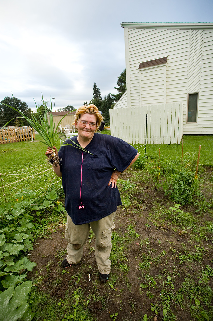 Nikki holds up an onion from the Grace House garden.